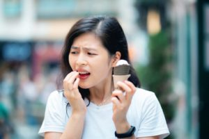 Woman with ice cream and sensitive teeth should see dentist