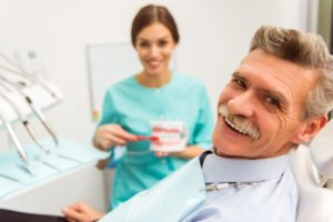 Smiling older man happy with his new dental implants
