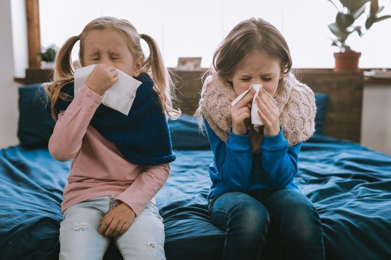 Two children blowing their nose
